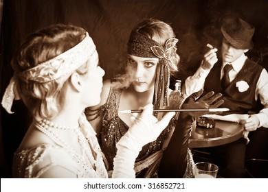 Flapper Girls und junger Gangster rauchen in der Bar