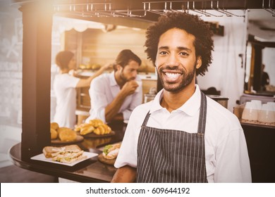 flare against handsome waiter smiling at camera
