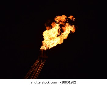 Flare boom nozzle and fire of offshore oil rig on night shift.