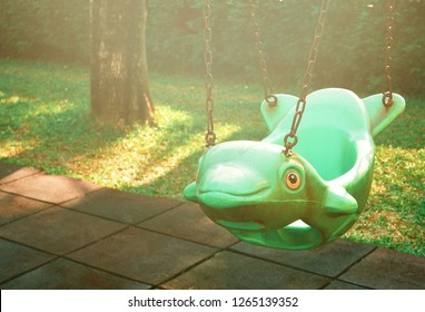 Flare light on surface of the old empty green hanging swing in dolphin shape and rubber floor tiles with green plants background in public park