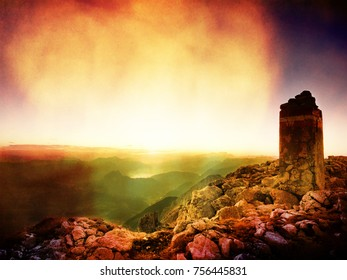Flare, soft focus.  Austria Germany border.  National border stone on Apine gravel  cliff. Daybreak horizon above blue foggy valley. Mountains increased from humidity
