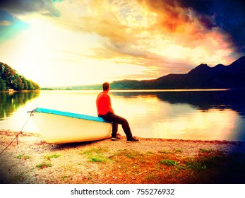 Flare, soft focus. Tiired man in red shirt sit on old fishing paddle boat at mountains lake coast. Vintage photo effect