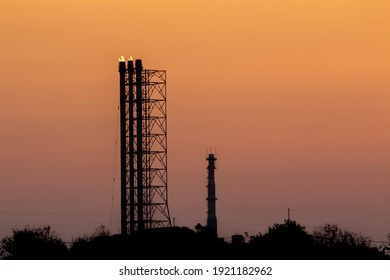 Flare stack or Ventilation industrial pressure chimneys and slight flames in the evening with a golden sky containing PM2.5 dust.