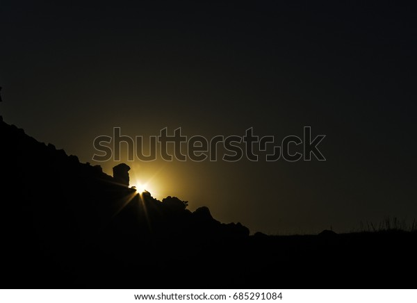 Flaring Sunset behind mountain silhouette