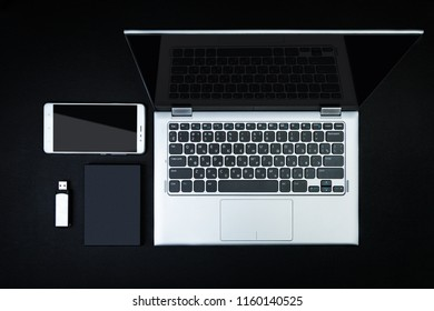 A flash drive, an external hard drive, smartphone and an open laptop on a black desk. The concept of mobile data storage. Flat lay