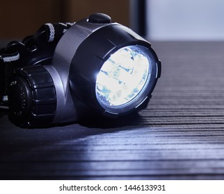Flash light head torch, with the beam switched on,it is on a dark surface.