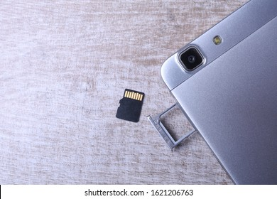 Flash memory data storage concept : A tray with a micro SD card on white background. A memory card is used for storing digital information in portable electronic devices e.g mobile phone, tablets