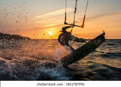 Flash photo of kitesurfer in beautiful yellow sunset at the baltic sea