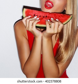 Flash style closeup portrait of sexy blonde with red lips eating red watermelon