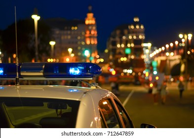 A flasher on the roof of a police car. Police. Background - city lights.