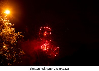 flashes of heart-shaped fireworks in the night sky under the light of a street lamp
