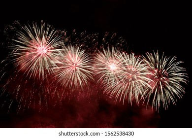 Flashes of red and white fireworks against the night black sky. Brightly ?olorful fireworks