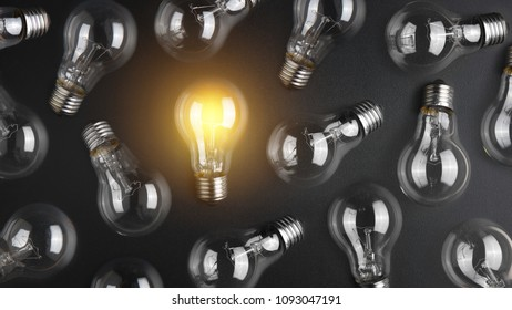 Flashing light bulb among a lot light bulbs on black desk. Idea concept
