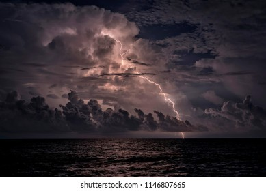 Flashing lightnings through the clouds above the night sea.