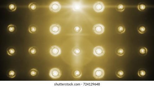 flashing shiny golden stage lights entertainment, spotlight projectors in the dark, gold warm soft light spotlight strike on black background