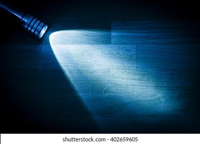 Flashlight and a beam of light in darkness. A modern led lamp with bright projection on dark wood table. Surface with copy space.