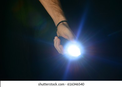 Flashlight in hand on a black background