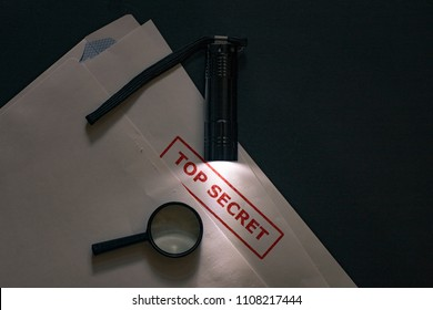 Flashlight illuminates the Top Secret document. On the envelope is a magnifying glass for espionage.