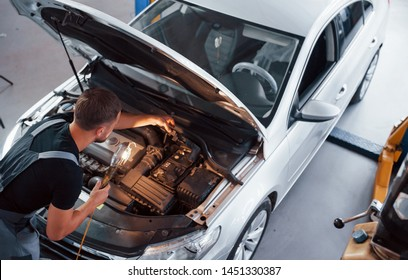 With flashlight. Man in grey uniform repairs white automobile indoors.