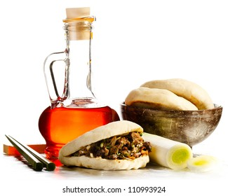 Flask of Chili oil with chinese hamburger and chopsticks