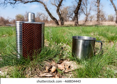 flask and cup on grass in spring forest