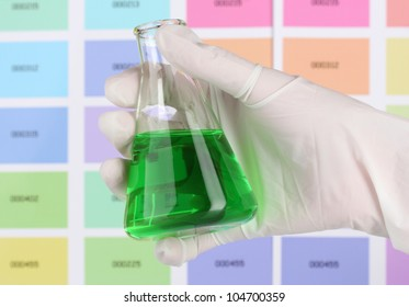 Flask with green liquid in hand on color samples background