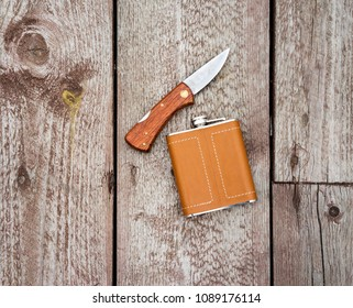 Flask in leather case and knife on the old wooden background