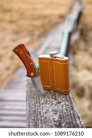 Flask in leather case and stuck knife on old wooden surface