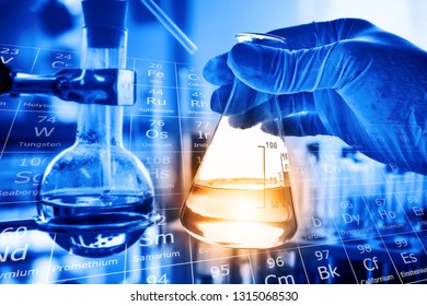 Flask in scientist hand with lab glassware background in laboratory. Science or chemical research and development concept.