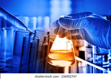 Flask in scientist hand with lab glassware background