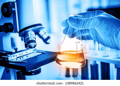 Flask in scientist hand with lab microscope background in laboratory. Science or chemical research and development concept.