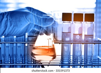Flask in scientist hand with test tubes, laboratory research concept