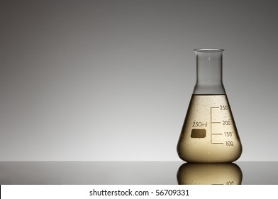 flask with yellow liquid to the light and white background