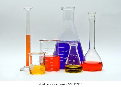 Flasks, cylinders and beakers with colorful liquids as pH indicators on a white background