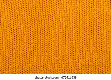 Flat background of orange knitted textile for designers