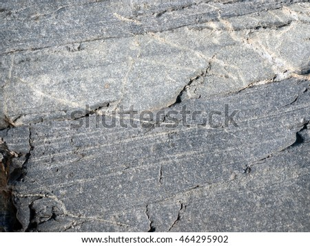 a968e59f60b3 A flat boulder with small cracks close-up. The stone is striped and has a  grayish color. Can be used as background - Image