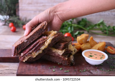 Flat Bread Brown Bread Beef and Cheese sandwich served with Chips and Sauce held over flat wooden plate.