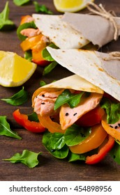 Flat bread with salmon and vegetables on a wooden background. Selective focus.