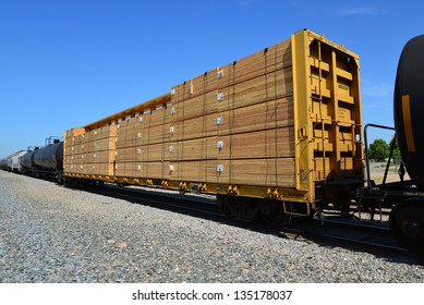 A flat car full of dressed construction lumber is sandwiched between oil tank cars