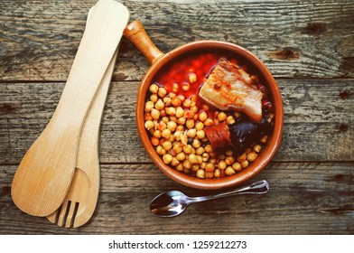 Flat of chickpeas, sausage and bacon in a crockpot by wooden spoon and fork. Typical food from Madrid, Spain, with a rustic wooden board as a background.