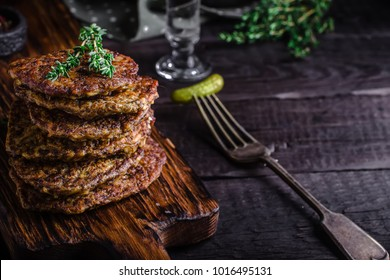 Flat cutlets on chopping board. Dark wooden background.Place for text. Selective focus.