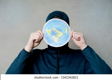 Flat Earther concept. Person who believes that Earth is flat disc. Anonymous hooded Man holding flat Earth model in front of face, copy space. Isolated on gray background, studio shot.