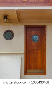 Flat of entrance wooden door with round window to the cabin on ship