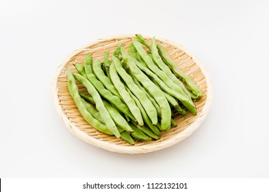 Flat green beans on bamboo sieve on white background