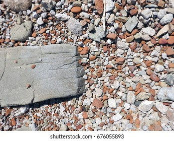 Flat large sea stone surrounded by shallow pebbles (textured abstract composition, suitable for background)