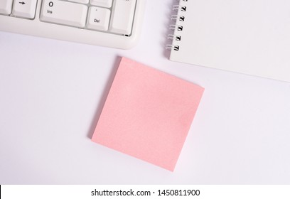 Flat lay above blank paper for text messages. Empty note paper on the white background by the pc keyboard with copy space.