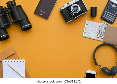 Flat lay of accessories on orange desk background of photographer, Voyage concept.
