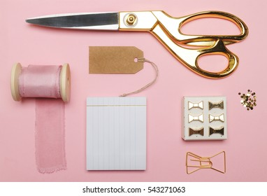 Flat lay. Accessories on the table, woman desk top. View top table, background mock up. Silk ribbon pink.