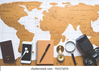 Flat lay, accessories for traveler, world map, passport, smart phone, in ear headphone, brown notebook, black luxury pen, gold compass, magnifying glass and black camera, top view, travel concept.