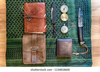 Flat lay adventure wanderlust travel kit: leather wallet, leather notepad, compass, pocket watch and knife lying on keffiyeh shemagh military neckerchief